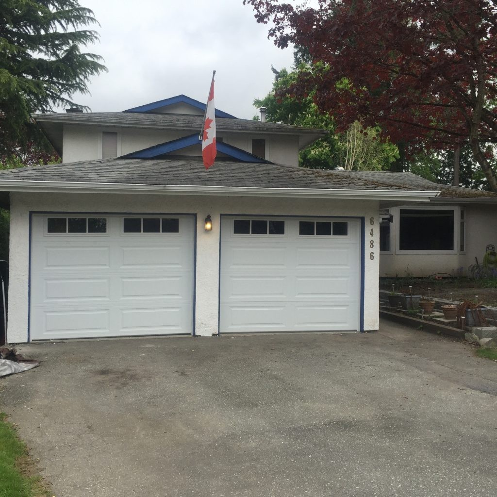 View of two installed 9x7 white insulated steel garage doors in Delta