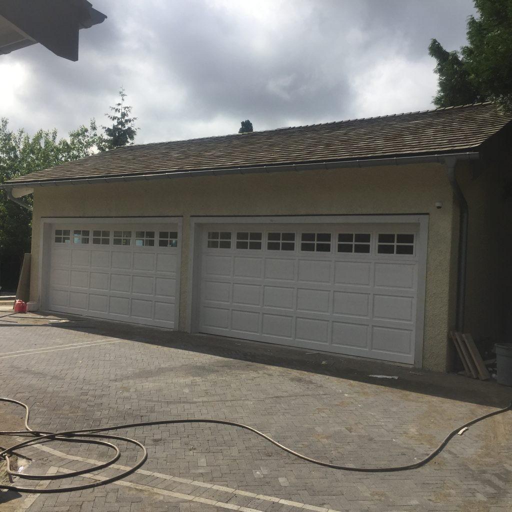 View of short panel garage door that has stockon window inserts.