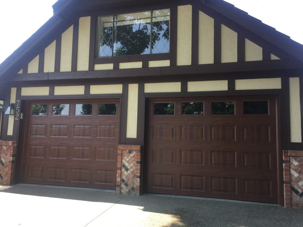 View of garage doors that have been installed with single glazed windows with wood texture.