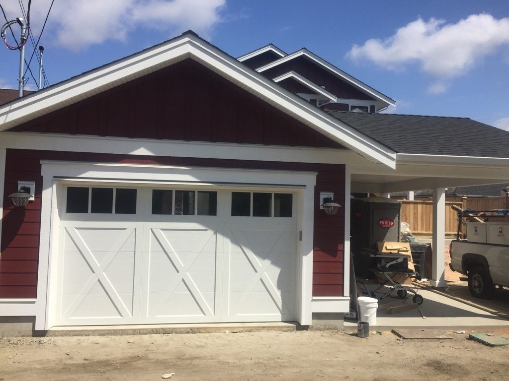 View of coachman style garage door with a clear glass top section in white.